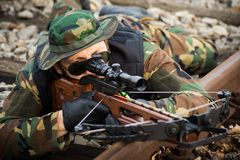 Military man aiming with crossbow. The military man is aiming with crossbow weapon and lying down on railway track Royalty Free Stock Images
