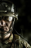 Military man in camouflage wearing helmet, glasses, radio set Stock Photos