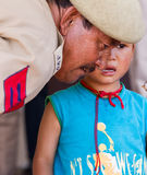 Military man comforting a crying baby boy Stock Photos