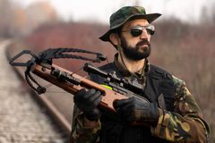 Military man with crossbow. Portrait of man in military uniform with crossbow weapon outdoors Royalty Free Stock Images