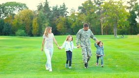Military man and family walking and having fun. Handsome caucasian soldier reunited with family on a sunny day in the park stock video footage