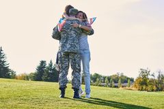 Military man father hugs daugther and wife. stock photo