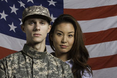 Military man and his wife in front of US flag, horizontal Royalty Free Stock Photography
