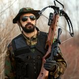 Military man with crossbow. The military man is holding crossbow weapon in hand outdoors Stock Image