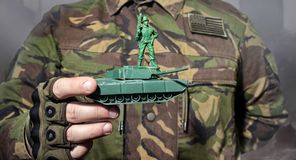 Military man holding a toy tank with soldier.