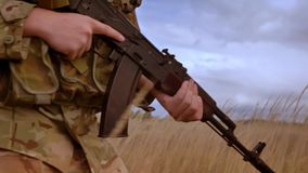 Military man is holding weapon and making confident steps through higher green grass outside, dark skies, defending. Authentic position stock video footage