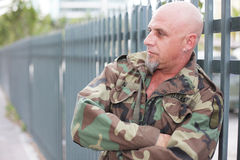 Military man leaning on the fence. Image of a military veteran leaning on the fence Royalty Free Stock Images