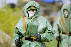 Military man in protective suit and gas mask outdoors. Are holding an automatic weapon Stock Images