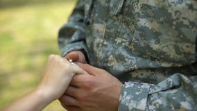 Military man putting engagement ring on woman hand, couple marriage, vow promise. Stock footage stock footage