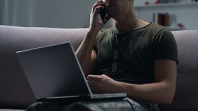 Military man talking on phone holding laptop, psychological support service. Stock footage stock video