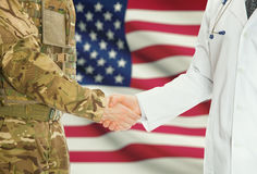 Military man in uniform and doctor shaking hands with national flag on background - United States Stock Photos