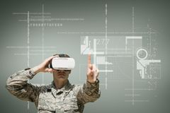 Military man in VR headset touching interface against green background with interfaces Stock Photo