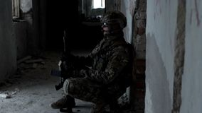 A military man with a weapon is ambushed in an abandoned building stock video