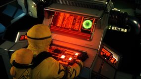 A military man in a yellow protective chemical clothing is working at a computer. A man in bacteriological protective