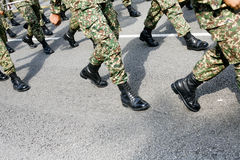 Military marching. A group of military men wearing camouflage uniform and black shiny boots marching on tarmac road Stock Image