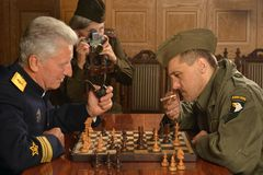 Military mature general playing chess with soldier Royalty Free Stock Photo