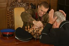 Military mature general playing chess with soldier Royalty Free Stock Images