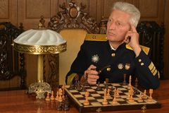 Military mature general playing chess Royalty Free Stock Photos