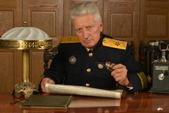 Military mature general on the table. Old military general sitting at the table Royalty Free Stock Images