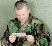 Military soldier reacts to a letter. An unshaven military man deployed in a war zone reacts to news he received from home.  This could be concern, surprising or Royalty Free Stock Photography