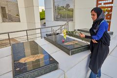 Military memorial in Sacred Defense garden-museum, Tehran, Iran. Tehran, Iran - April 28, 2017: Iranian woman in hijab puts flower on tombstone of Military stock images