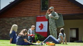 Soldier with family on green backyard stock image