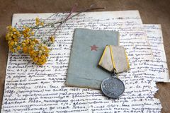 Military merit medal, old letter on canvas. Relics, close-up. Dry flowers of tansy royalty free stock image