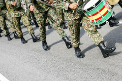 Military music band march. A group of military men wearing camouflage uniform and black shiny boots marching on tarmac road Royalty Free Stock Photos