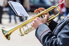 Military musician playing on gold trumpet in army orchestra Stock Photography