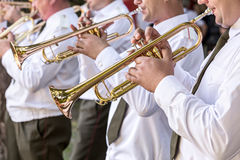 Military musicians blowing gold trumpets Stock Image