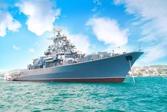 Military navy ship. In the bay with blue sky and clouds stock image