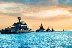 Military navy ships in a sea bay. At sunset time Stock Photos