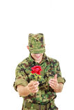 Military officer holding flower smiling shy with head bowed Royalty Free Stock Photo