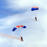 Military parachute jump celebration. Paratroopers descending in a military skydiving parachute demonstration Stock Images