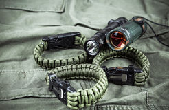 Military paracord bracelet, tactical torch and spy-glass. On army-green fabric royalty free stock images