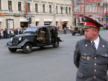 Military parade in Saint-Petersburg, Russia. Old car drives the road, a man in old military uniform greets the public from the car. A policeman watches the order stock photography