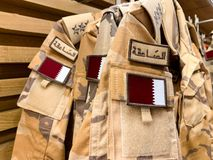 Military pattern workwear with the Qatari flag hanging in a row. April 2019, Doha/ Qatar.  royalty free stock photos