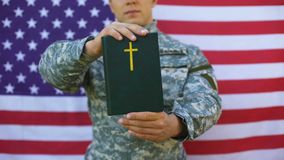 Military peacekeeper showing bible, american flag background, faith symbol hope