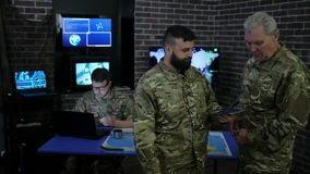 Military personnel, commander and soldier, in military headquarters, view digital tablet, stock footage