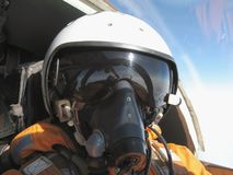 The military pilot in the plane. In a helmet in dark blue overalls against the blue sky Stock Image