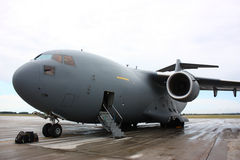 Military plane. A military transportation jet plane C17-Globemaster on a runway with open door and luggage in-front of the airplane royalty free stock photos