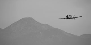 Military Plane. This is a black and white photo of a classic United States military plane in flight with mountains in the background Stock Photos