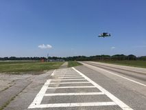 Military planes landing. Military plane landing while crossing a road and blue sky background Stock Photos