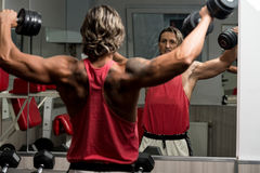 Military Press with Dumbbells. Bodybuilder exercising military press with dumbbells royalty free stock photography