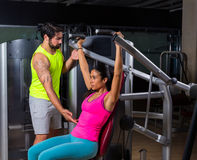 Military press machine woman personal trainer Stock Image