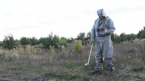 Military in a protective suit checks the level of radiation on the road dosimeter, radiation hazard, military. Military in a protective suit checks the level of stock footage