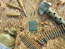 Military rank with ammunition from World War 2 and drinking bottle. Laying outside in straw royalty free stock images