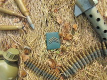 Military rank with ammunition from World War 2 and drinking bottle. Laying outside in straw stock photography