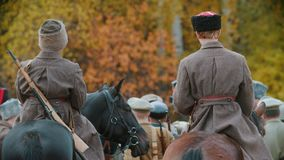 A military reconstruction - an area surrounded by soldiers - men standing on the horses on the field. Mid shot stock video footage