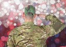 Military saluting against glowing background. Digital composite of Military saluting against glowing background Stock Images
